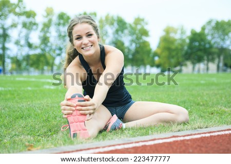 Stretching leg young woman jogging track  - stock photo