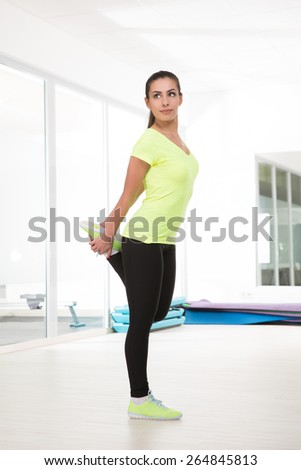 Stretching one leg before running. Beautiful sporty woman in gym - stock photo