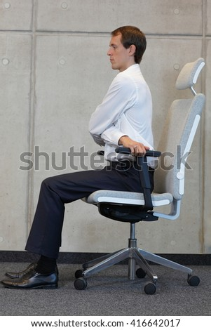 stretching with chair in office - business man exercising  - stock photo