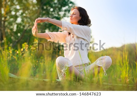 Stretching woman in outdoor exercise smiling happy doing yoga stretches. Beautiful happy smiling sport fitness model outside on summer / spring day - stock photo