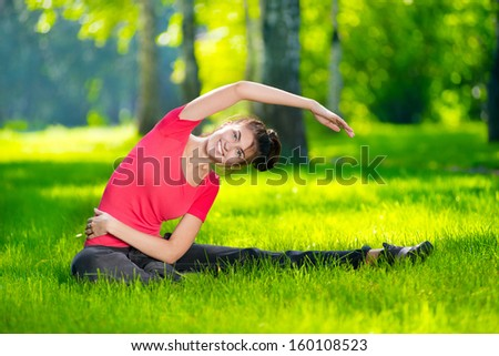 Stretching woman in outdoor sport exercise. Smiling happy doing yoga stretches after running. Fitness model outside in park at summer day.  - stock photo