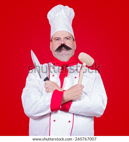 strict cook holding knife and beater - stock photo