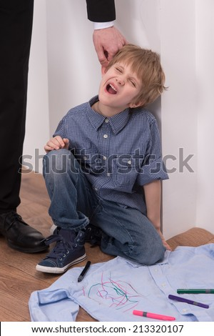 Strict father punishes naughty son. Isolated on white background boy sitting on floor  - stock photo