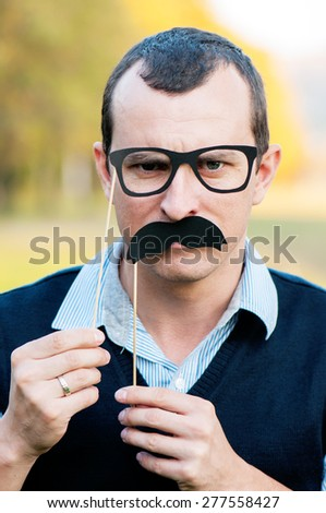 strict man with decorative glasses and moustaches on a stick looks in the camera - stock photo