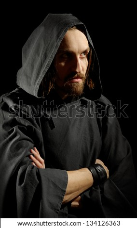 strict monk in cape, black background - stock photo