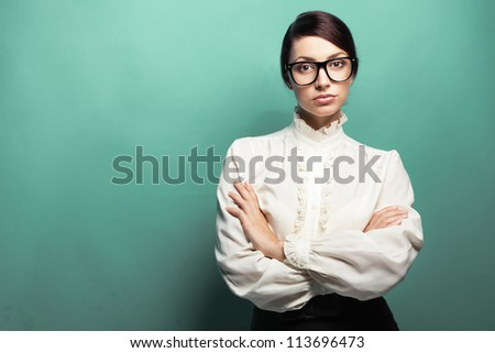 Strict woman in large glasses, green background - stock photo