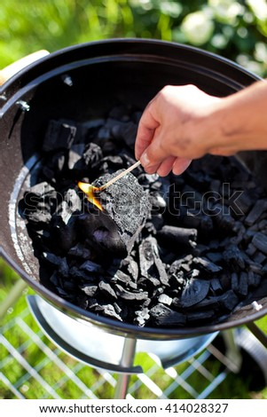Striking a matchstick, burn up a charcoal in barbecue grill, prepare for cooking - stock photo