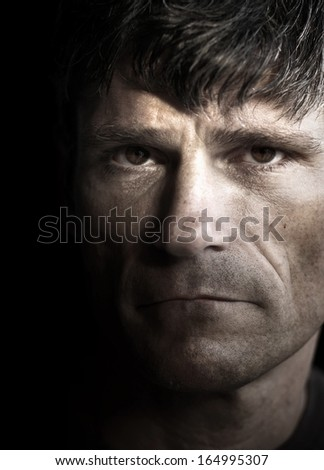 Striking dark close up portrait of a sad man - stock photo