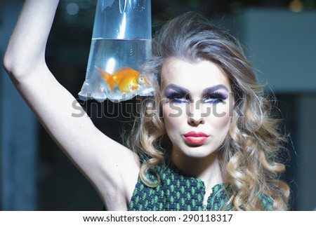 Striking young girl with bright makeup and blonde curly hair holding cellophane package aquarium with goldfish, horizontal photo - stock photo