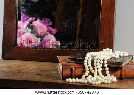 String of pearls, books and antique mirror.  Focus on pearls. - stock photo