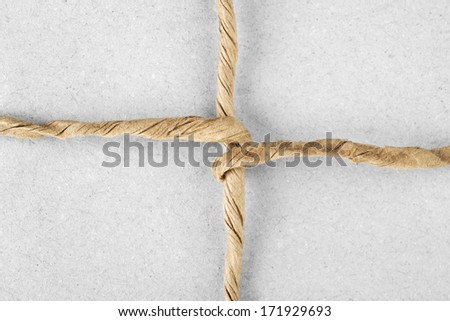 String tied in a bow on  packaging paper - stock photo