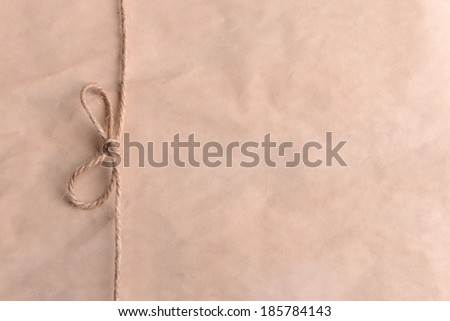 String tied in  bow on beige paper packaging close-up - stock photo