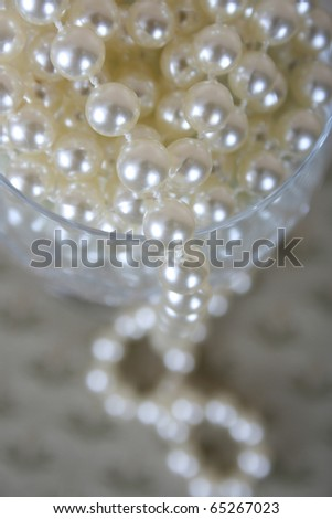 Strings of pearls in a crystal glass - stock photo
