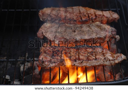 Strip loin steaks on the barbecue - stock photo