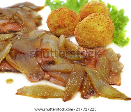 Strip steak roasted with onion and served with potatoes croquettes, main menu dish, close up - stock photo
