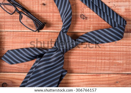 Stripe neck tie and glasses on old wooden table - stock photo