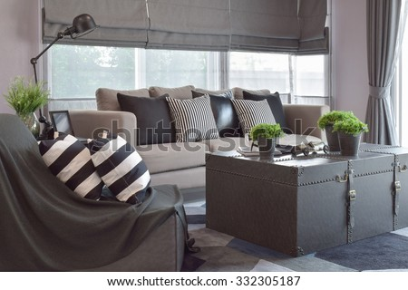 Striped and black leather pillows on the sofa in modern industrial style living room - stock photo