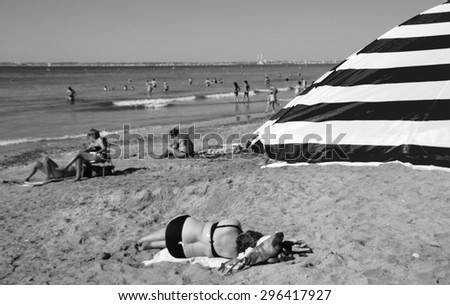 Striped beach umbrella and blurred people at background. Trouville-sur-Mer (Normandy, France). Selected focus on umbrella. Aged photo. Black and white. - stock photo