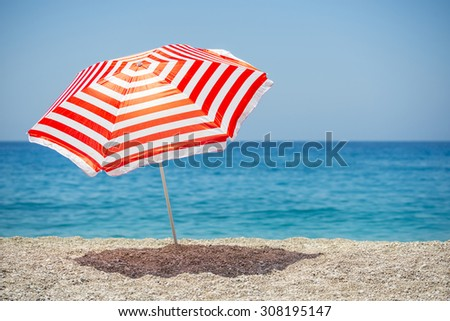 Striped beach umbrella on the beach. - stock photo