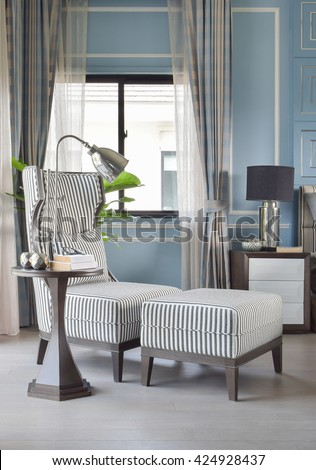 Striped high back armchair with ottoman in light blue classic bedroom - stock photo