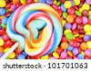 Striped lollipop and multicolored smarties - stock photo