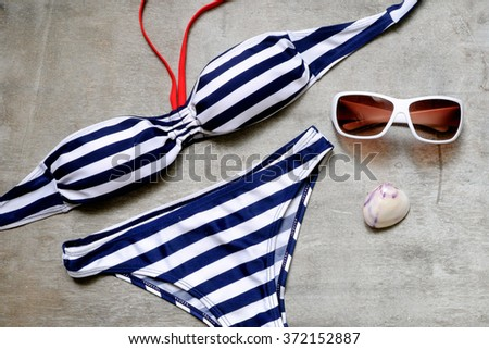 striped swimsuit and sunglasses on a gray wooden background.  Top view - stock photo