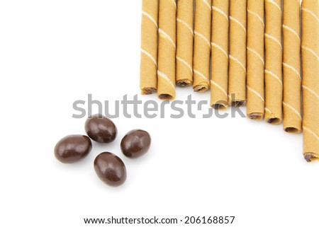 Striped wafer rolls filled with a mixture of chocolate and sphere chocolate on a white background - stock photo