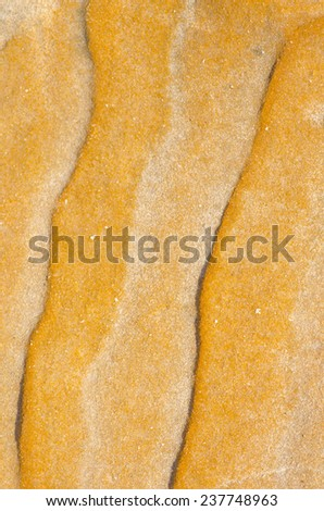 Striped wavy natural pattern and texture of sandy grain of orange rock outdoor, backdrop, background or wallpaper with copy space. - stock photo