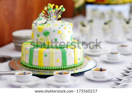 Striped wedding cake decorated with yellow and green flowers - stock photo