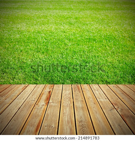 Striped wooden plank terrace with the view to green grass background - stock photo
