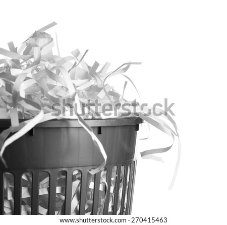 Strips of destroyed paper from shredder in trash can isolated on white - stock photo