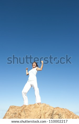 Strong and confident attractive mature woman on top of a mountain, isolated with blue sky as background and copy space. - stock photo
