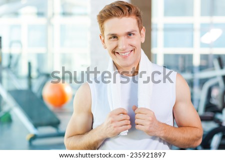 Strong and confident. Confident young muscular man carrying towel on shoulders and smiling while standing in gym - stock photo