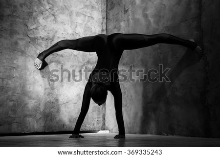Strong and flexible. Monochrome portrait of a gymnast woman making splits while standing on her hands against the wall - stock photo