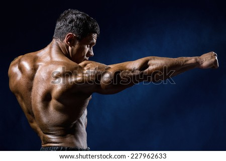 Strong Athletic Man Fitness Model shows the kick.  - stock photo