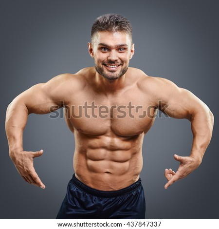 Strong Athletic Man Fitness Model Torso pointing down. Smiling muscular bodybuilder showing his strong body. - stock photo