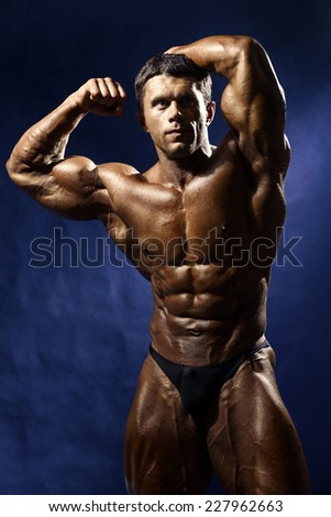 Strong Athletic Man Fitness Model Torso showing big muscles. Champion on a dark blue background - stock photo