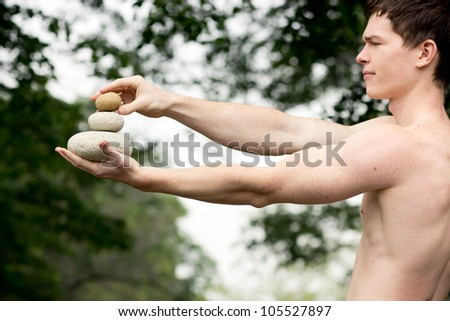 Strong athletic man holding a pile of stones in balance. Get the balance concept. - stock photo