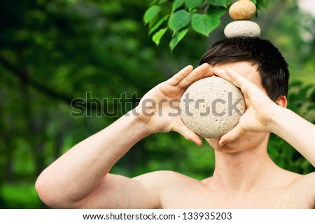 Strong athletic man holding a pile of stones in balance on his head, covering his face with a stone. Get the balance concept. - stock photo