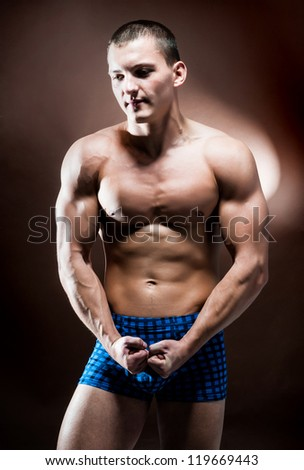 strong athletic man on a brown background - stock photo