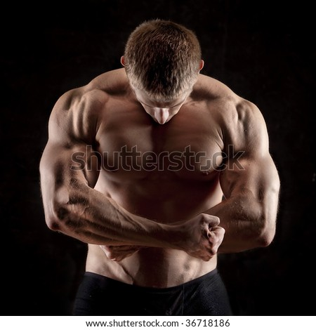 strong athletic man on black background - stock photo
