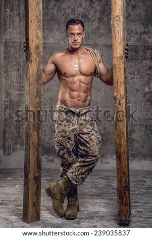 strong athletic man with naked body in military pants with wooden beams and rope on concrete wall - stock photo