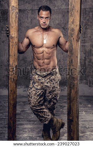 strong athletic man with naked body in military pants with wooden beams on concrete wall - stock photo