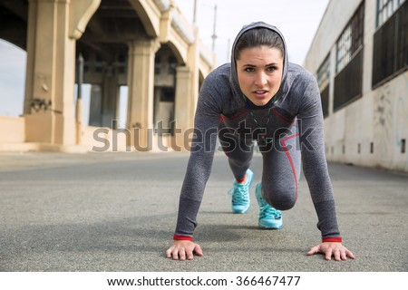 Strong athletic toned female athlete in sportswear with hoody training with push ups outdoors - stock photo