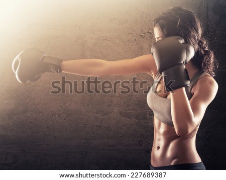 Strong athletic woman with boxing gloves punching - stock photo