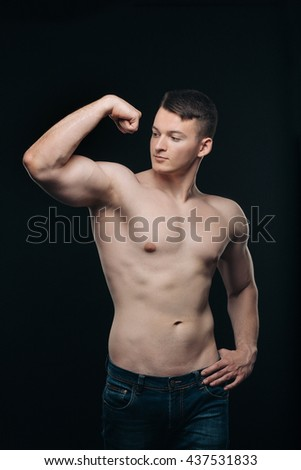 Strong athletic young  man on black - stock photo