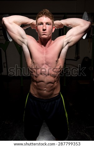 Strong attractive man working out with weights at a gym. Used dramatic lighting to convey determination, motivation, and focus. - stock photo