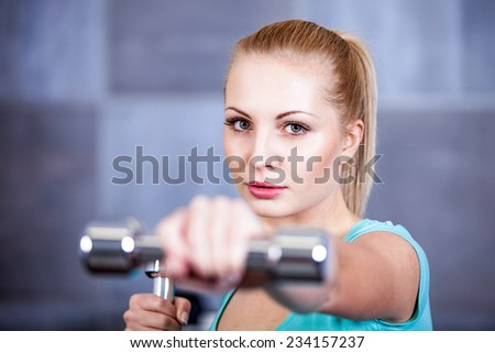 Strong blonde woman weightlifting at the gym, doing shoulders exercise - stock photo