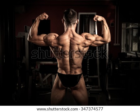 Strong bodybuilder flexing his back in the gym - stock photo