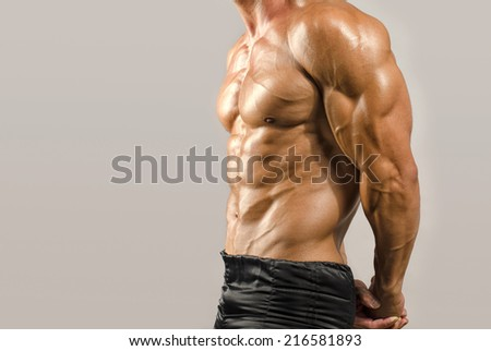Strong bodybuilder man with perfect abs, shoulders,biceps, triceps and chest, personal fitness trainer - stock photo